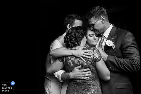 Black and white photo of the bride and groom in a group hug with guests by a Washington, D.C. wedding photographer.