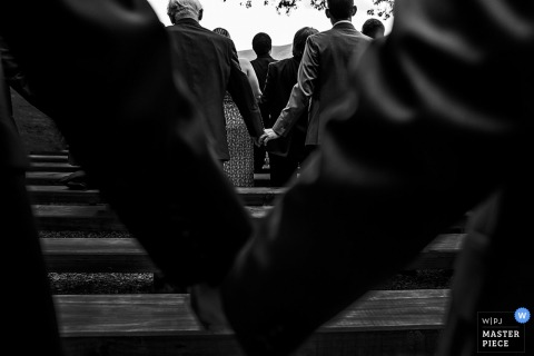 Black and white photo of men holding hands during the ceremony by a Washington, D.C. wedding photographer.