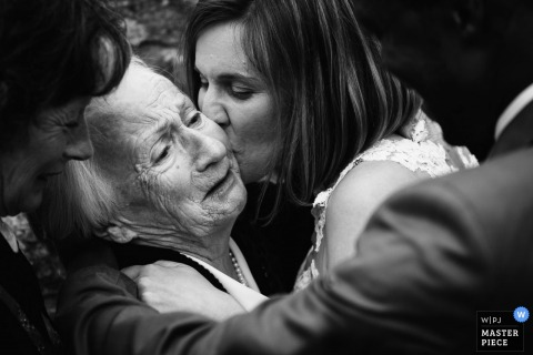 Black and white photo of the bride kissing a woman on the cheek by a Playas de la Loire, France wedding photographer.