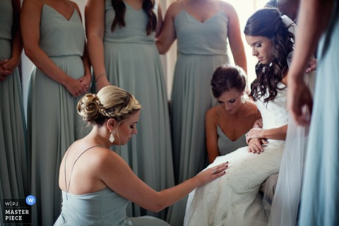 The bride is surrounded by her bridesmaids, one of whom touches her lap in this photo by a Denver, CO wedding photographer.