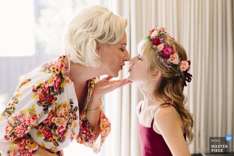 Photo of a woman kissing her young relative wearing a crown of flowers by a Boston, MA wedding photographer.