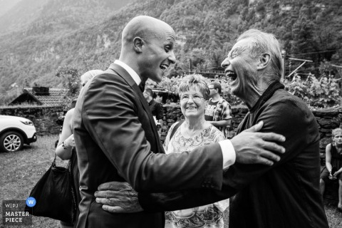 Black and white photo of two men greeting each other excitedly by a Lombardy wedding photographer.