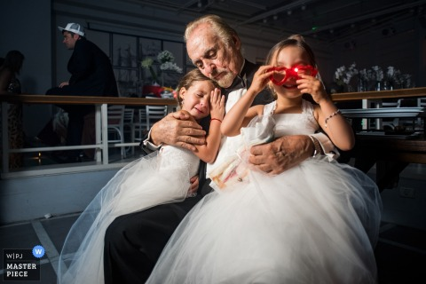 Photo of a man holding two young girls as one plays with red sunglasses by a Madrid, Spain wedding photographer.