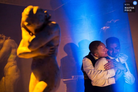 Photo of a man hugging another from behind next to a statue by a San Francisco, CA wedding photographer.