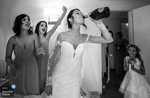 Black and white photo of the bride drinking from a bottle of champagne as her bridesmaids cheer her on by a Tuscany wedding photographer.