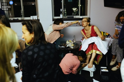 Photo of a woman giving the bride a sip of wine as she gets her nails done by a London, England wedding reportage photographer.