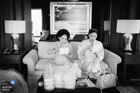The bride and another woman sit on a couch together eating food in this black and white photo by a Bangkok, Thailand wedding photographer.