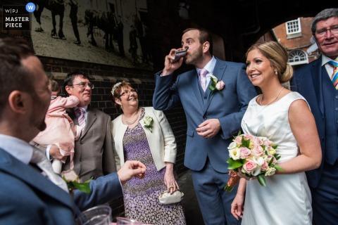 Les mariés quittent la cérémonie ensemble alors que le marié sirote une fiole sur cette photo, réalisée par un photographe de reportage de mariage de Kent, en Angleterre.