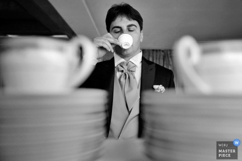 Black and white photo of a man sipping espresso taken through stacks of plates and cups by a Calabria wedding photographer.