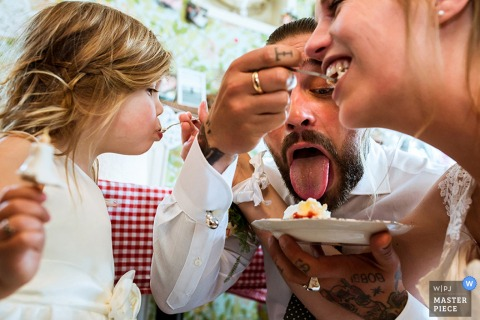Photo du marié qui nourrit un morceau de gâteau avec la mariée, comme elle nourrit une jeune fille, et le marié fait semblant de lécher l'assiette par un photographe de mariage à Rotterdam.