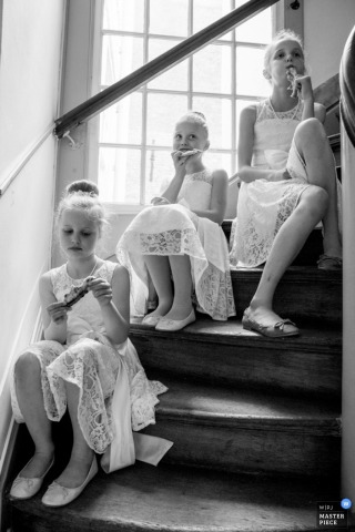 Black and white photo of three young girls in white dresses sitting on a staircase and having a snack by a Netherlands wedding photographer.