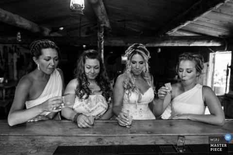 Die Braut und ihre Brautjungfern machen einen Schuss an der Bar in diesem Schwarzweißfoto von einem Hochzeitsfotografen in Alberta, Kanada.