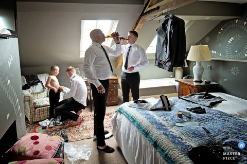 Photo of two men drinking beer as another man helps a young boy get ready before the ceremony by a Devon, England wedding reportage photographer.