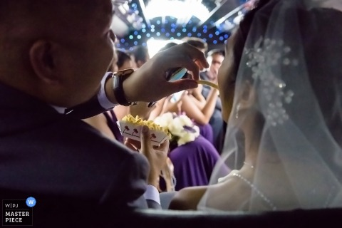 Photo of the groom feeding his bride - shot from behind by a Santa Barbara wedding photographer.