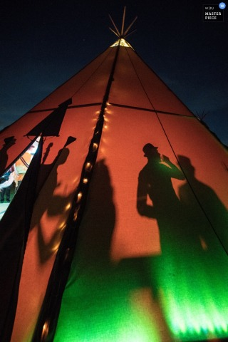 Photo of guests' shadows inside a large tepee at night by a London, England wedding reportage photographer.