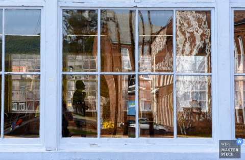 Zdjęcie scenerii odbijające się w oknach holu recepcyjnego z mężczyzną w środku sylwetką nowojorskiego fotografa ślubnego.