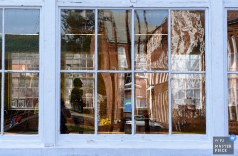 Foto van landschap weerspiegeld in de ramen van de ontvangsthal met een man binnen gesilhouetteerd door een New York huwelijksfotograaf.