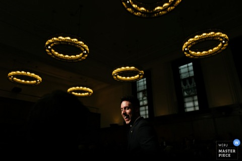 Photo of a man laughing in a dimly lit room beneath circles of lights by a London, England wedding reportage photographer.