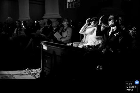 Photo noir et blanc d'invités protégeant leurs yeux d'un rayon de soleil alors qu'ils assistent à la cérémonie organisée par un photographe de mariage à Rotterdam.