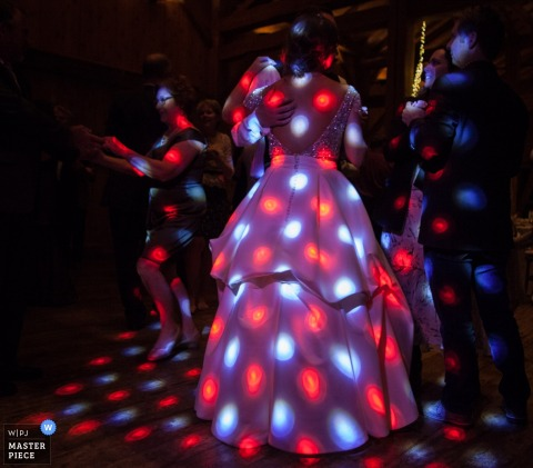 Photo of the bride on the dance floor lit up by disco lights by a Montana wedding photographer.