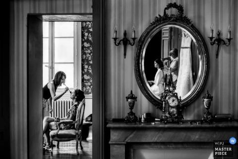 Zwart-witte foto van een vrouw die haar make-up gedaan krijgen aangezien de bruid en haar kapper in een spiegel op de muur door een het huwelijksfotograaf van Montpellier worden weerspiegeld.