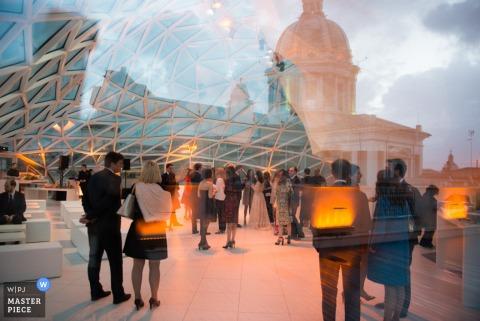 Foto der Gäste, die durch ein Fenster mit der einzigartigen Architektur genommen werden, die in der Reflexion von einem Rom-Hochzeitsfotografen sichtbar ist.