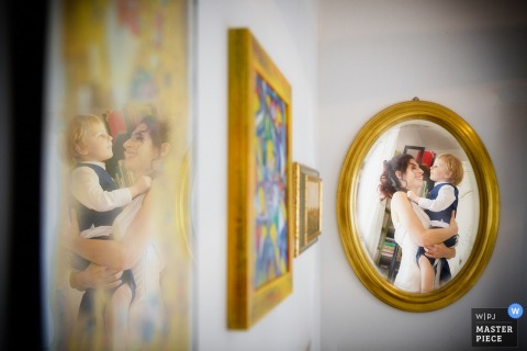 Photo of pictures on the wall with one, a photo of the bride holding a young boy, reflected on the adjacent wall by a Venice wedding photographer.
