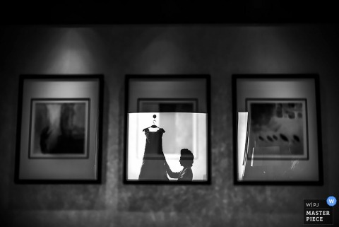 Black and white photo of the bride with her dress hanging reflected in pictures on a wall by a Bangkok, Thailand wedding photographer.