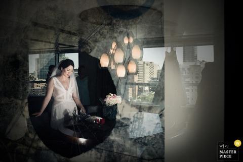 Foto der Braut in ihrem Raum reflektierte sich in einem Fenster von einem Hochzeitsfotografen Montreals, Quebec.