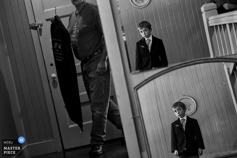 Black and white photo of a young boy reflected in two mirrors as a man walks around the corner holding a suit by a Lake Tahoe, CA wedding photographer.