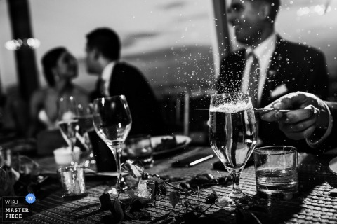 Black and white detail photo of water splashing out of a glass as a guest taps it with a knife by a Washington, D.C. wedding photographer.