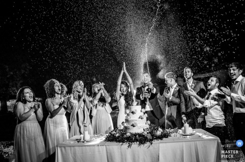 Black and white photo of a toast to the bride and groom as champagne bursts from its bottle by a Turin, Italy wedding photographer.