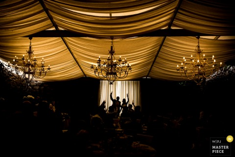 Photo of guests silhouetted while giving a toast in a tent beneath large chandeliers by a Turin, Italy wedding photographer.