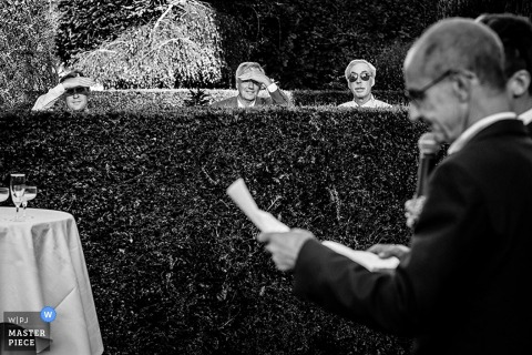 Black and white photo of guests peering over a hedge to listen to the speech by a Paris wedding photographer.