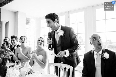 The best man has the bridal party laughing during his speech in this black and white photo by a Hampshire, England wedding reportage photographer.