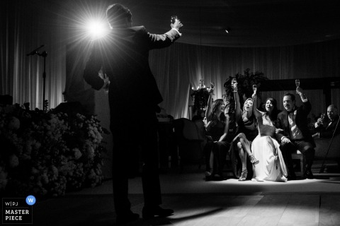 Black and white photo of a guest toasting the bride and groom by a Houston, TX wedding photographer.