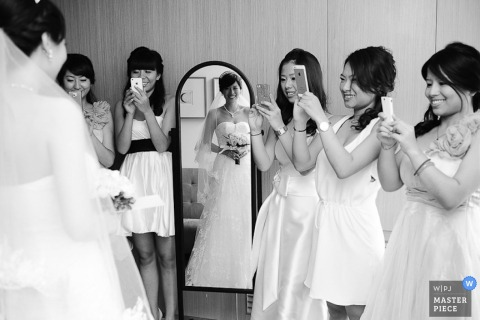 The bridesmaids take pictures of the bride, reflected in the mirror, with their phones in this black and white photo by a Taipei, Taiwan wedding photographer.