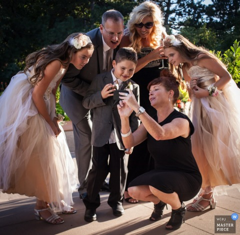 Photo of a family leaning over to look at pictures on a phone together by Montana wedding photographer.