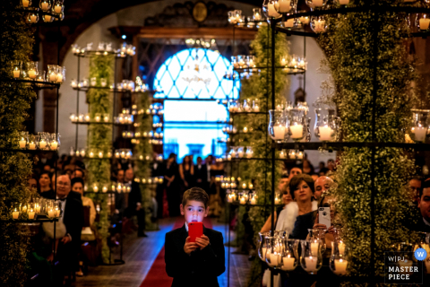 A young boy stands in the aisle surrounded by candles, holding up a phone in this photo by a San Diego, CA wedding photographer.
