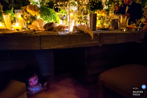 A young girl sits under a table playing on her phone during the reception in this photo by a San Diego, CA wedding photographer.