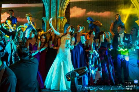 La novia se toma un selfie en la sala de recepción rodeada de invitados en esta foto de un fotógrafo de bodas de San Diego, California.