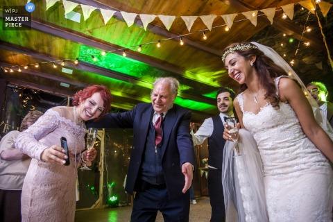 Een vrouw toont de bruid een foto op haar telefoon tijdens de receptie op deze foto door een huwelijksfotograaf uit Armenië.