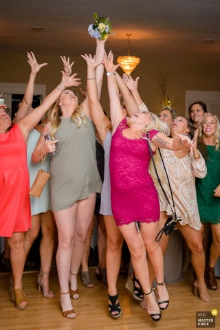 Several woman reach their arms up trying to catch the bride's bouquet in this photo by a Minneapolis, MN wedding photographer.
