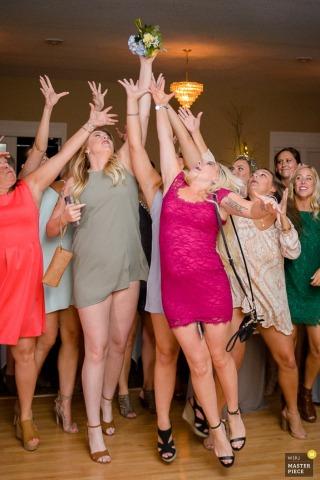 Kilka kobiet wyciąga ręce, próbując złapać bukiet panny młodej na tym zdjęciu przez fotografa ślubnego z Minneapolis, MN.