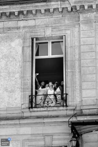 Black and white photo of the bride and her bridesmaids taking a selfie by a large window by a Paris wedding photographer.