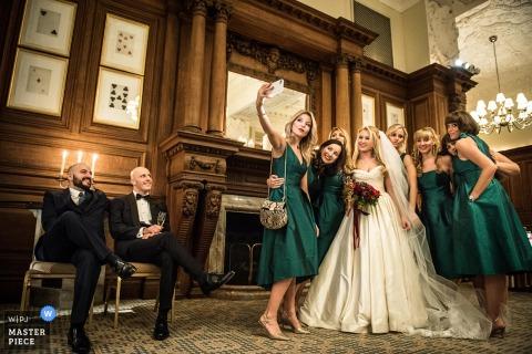 Die Braut und ihre Brautjungfern machen zusammen ein Selfie, während andere auf diesem Foto von einem Hochzeitsreportagefotografen aus London, England zusehen.