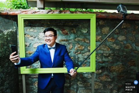 Foto van een man die een selfie neemt terwijl hij in een groot, leeg frame staat door een huwelijksfotograaf uit Lyon, Frankrijk.