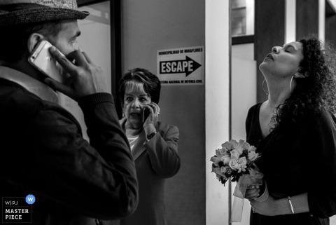 Czarno-białe zdjęcie gości na telefonach oczekujących na ceremonię przez fotografa ślubnego z Limy w Peru.