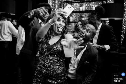 Three guests take a lighthearted selfie during the reception in this photo by a Houston, TX wedding photographer.