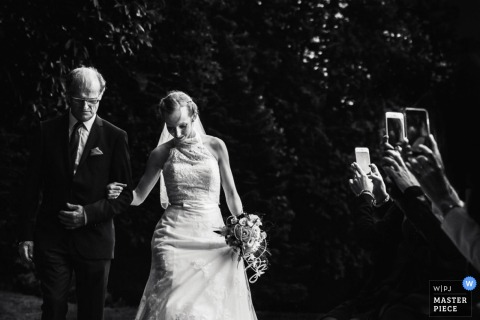 Guests use their phones to take pictures of the bride and her father as they walk down the aisle in this black and white photo by a Paris wedding photographer.